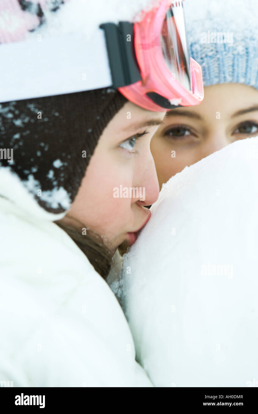 Teenage girl kissing snowball, close-up, friend in background - Stock Image
