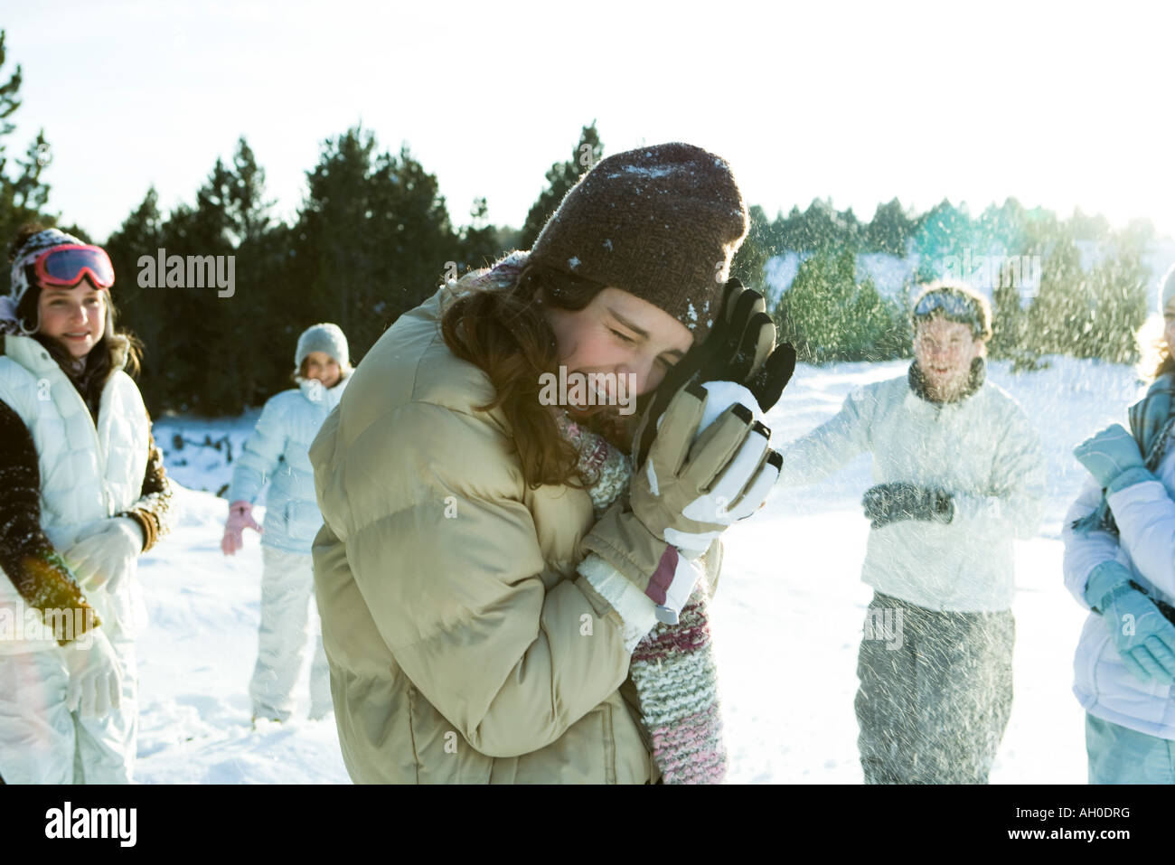 Young friends throwing snowballs, smiling, blurred motion Stock Photo