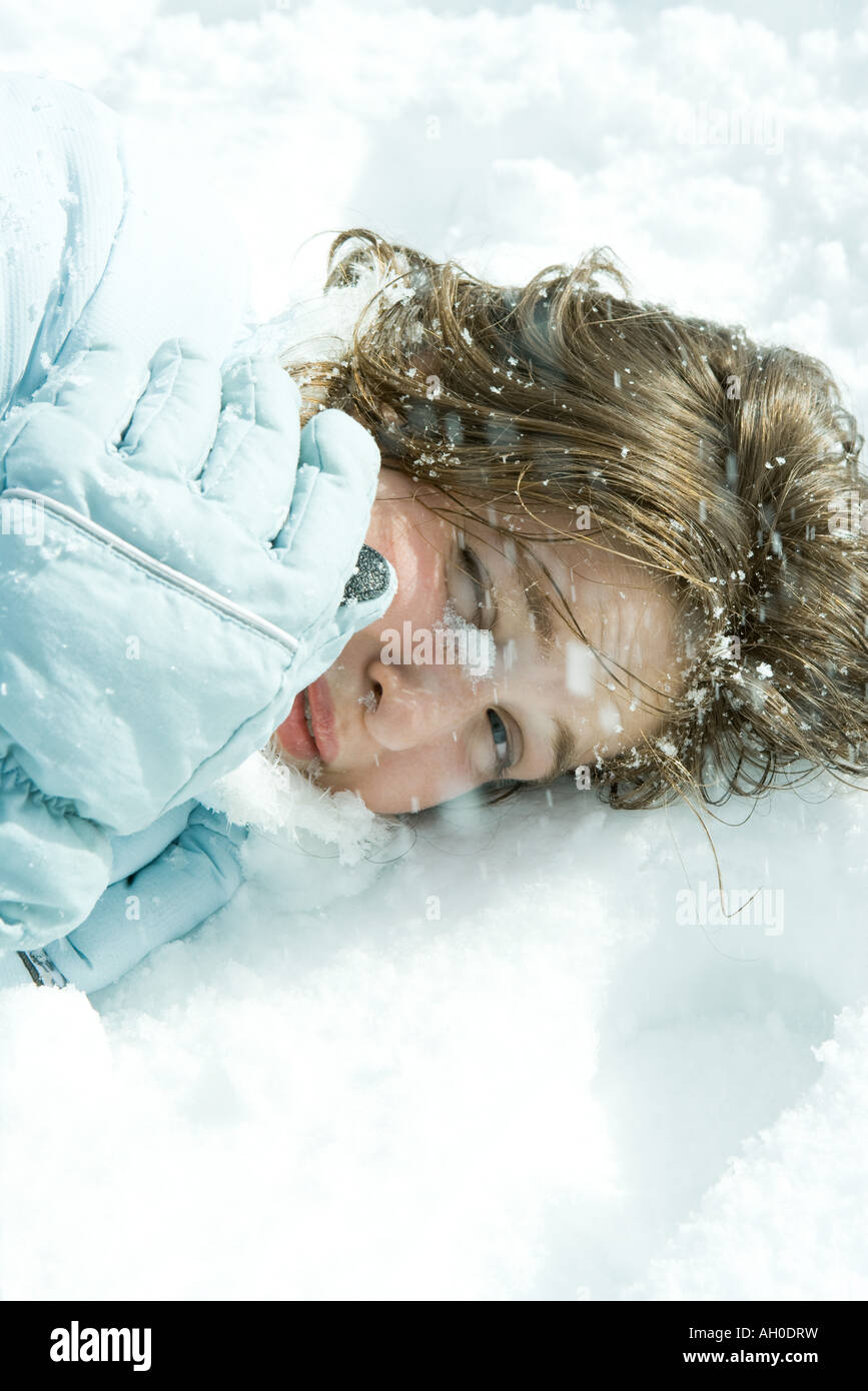 Teenage girl reclining in snow, looking at camera, close-up - Stock Image