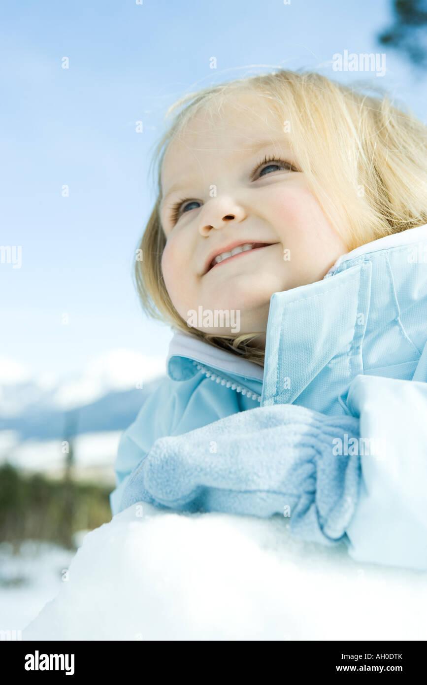 Toddler girl in snow, smiling, looking away - Stock Image