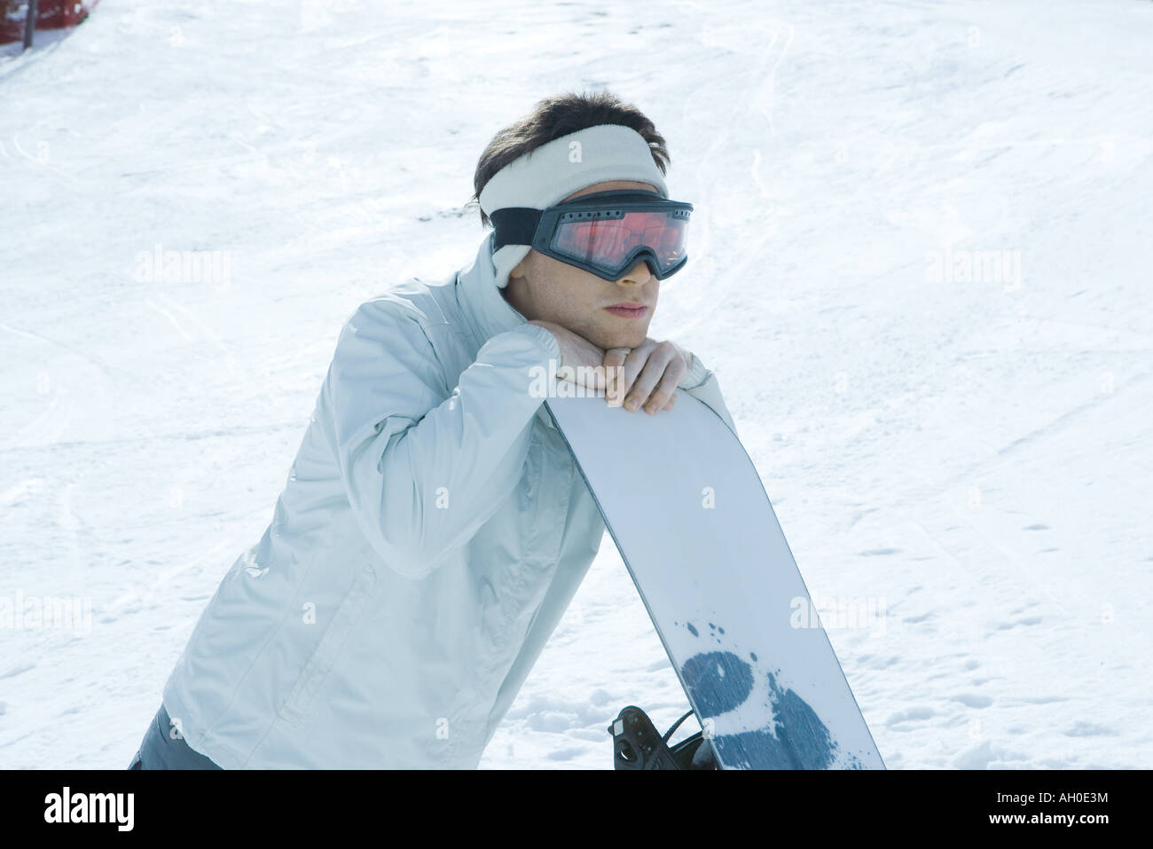 Young man leaning on snowboard Stock Photo