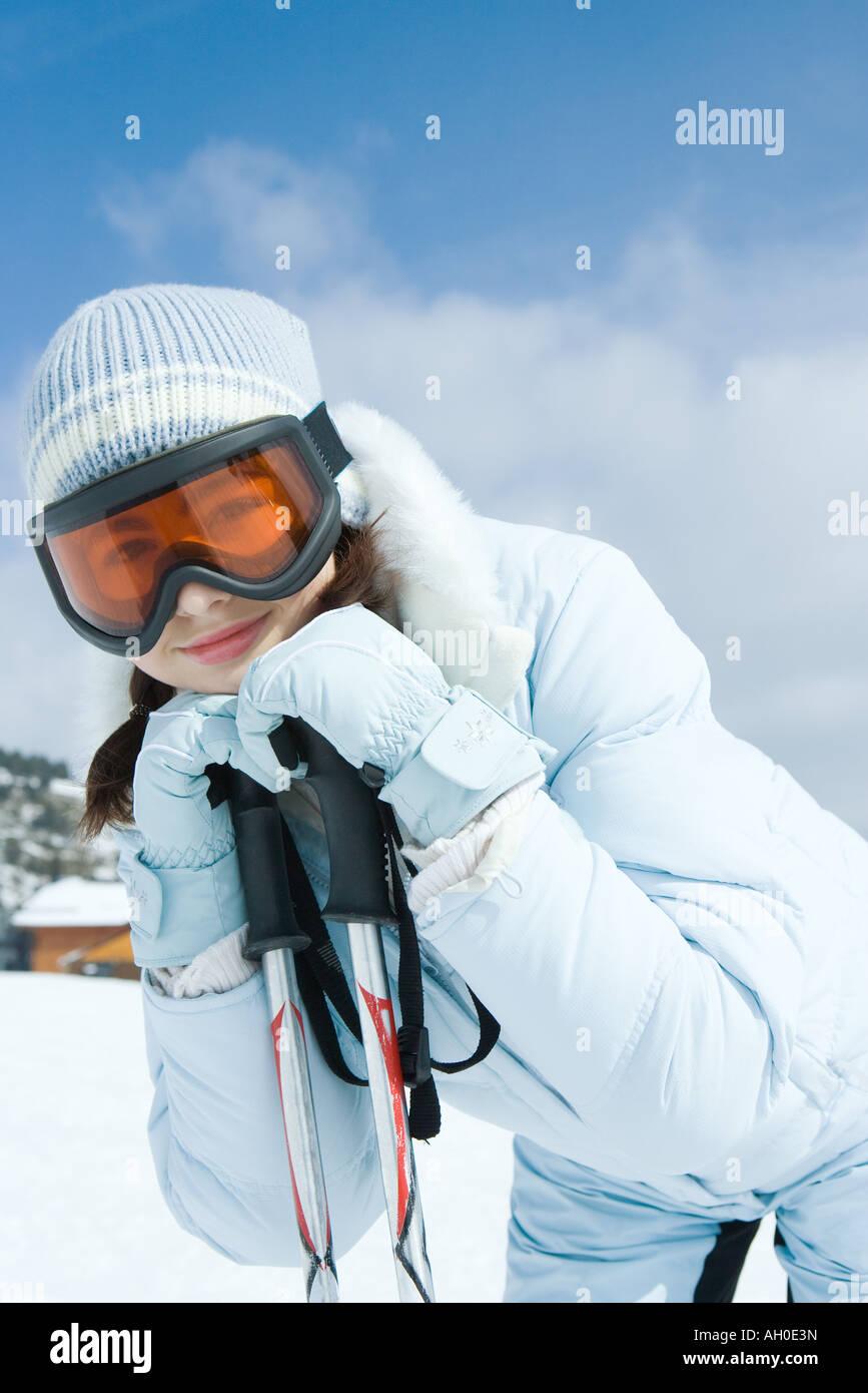 Teen girl leaning on ski poles, smiling at camera - Stock Image