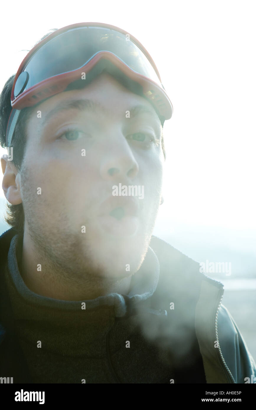 Young Man Breathing Out Into Cold Air   Stock Image
