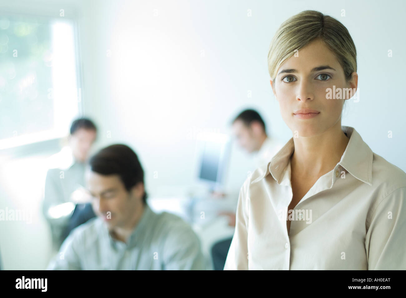 Young businesswoman looking at camera, head and shoulders, associates in background - Stock Image