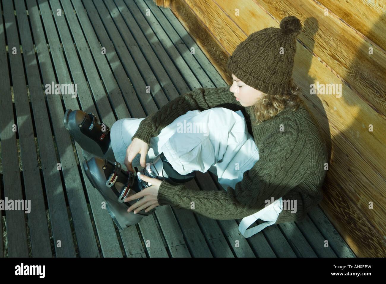 Teenage girl sitting on ground, putting on ski boot - Stock Image