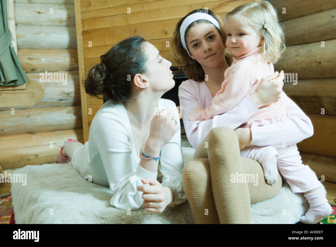 Two teenage girls sitting on bed, one holding toddler on lap - Stock Image