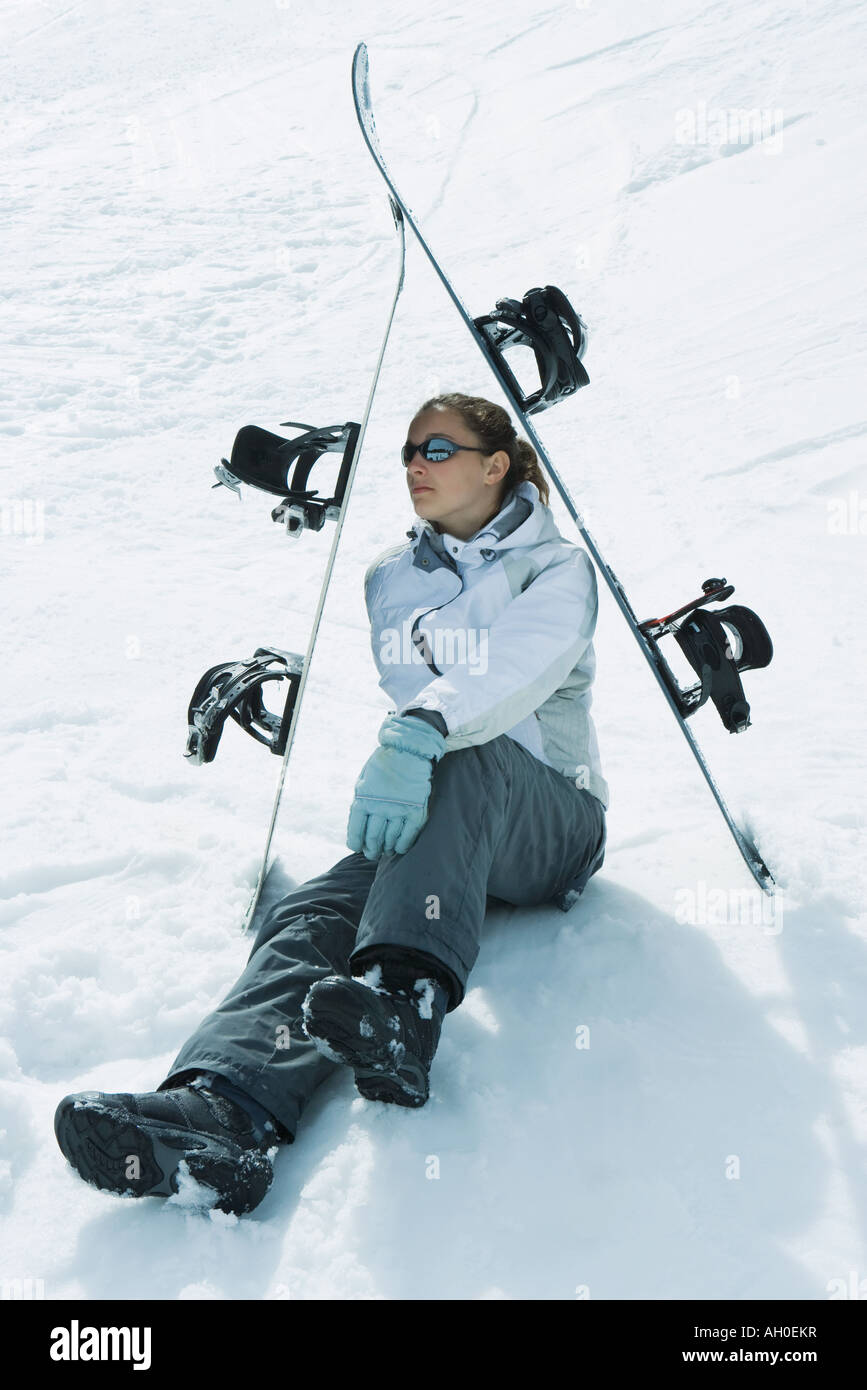 Young female skier sitting on the ground under skis, looking away Stock Photo