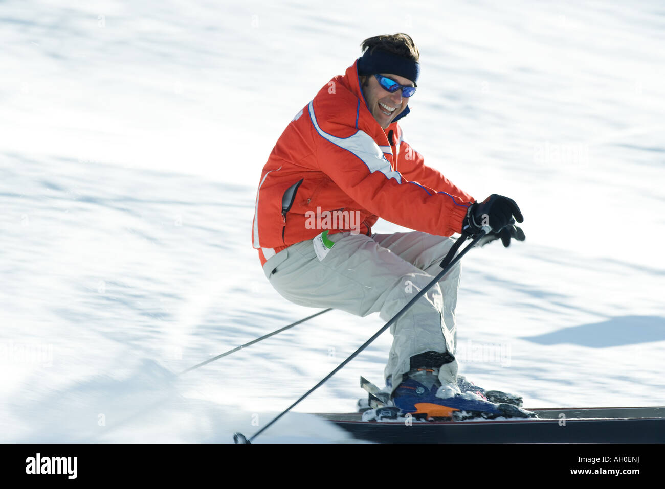 Mature male skier on ski slope, smiling toward camera, blurred motion Stock Photo