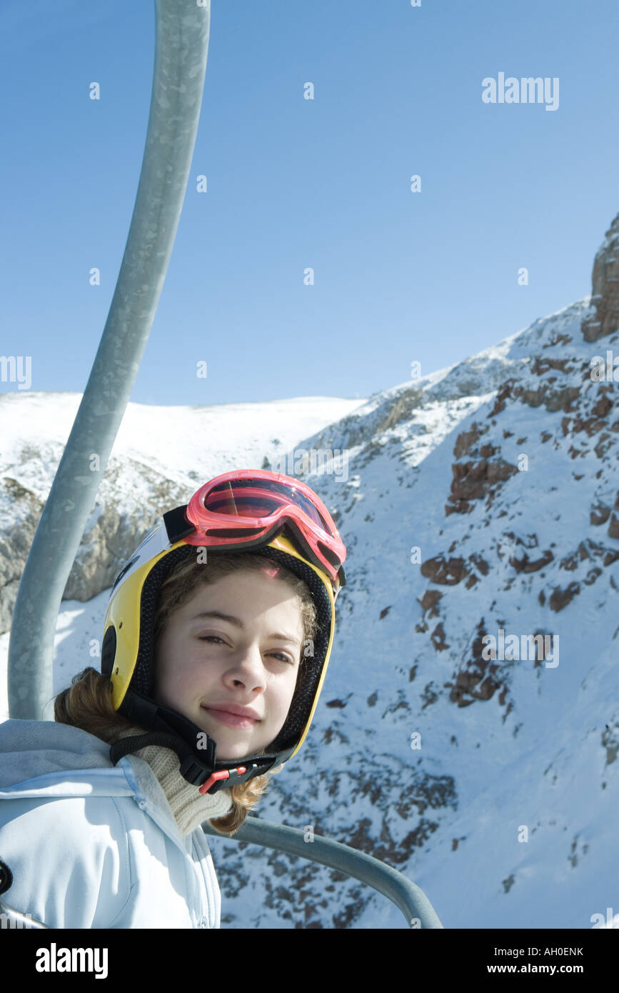 Teenage girl in chair lift, dressed in ski clothing, smiling at camera - Stock Image