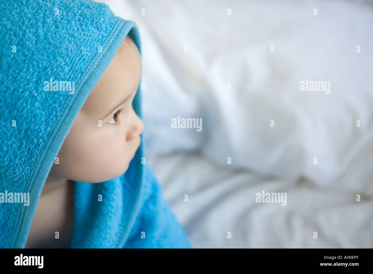 Baby wrapped in towel, looking away - Stock Image