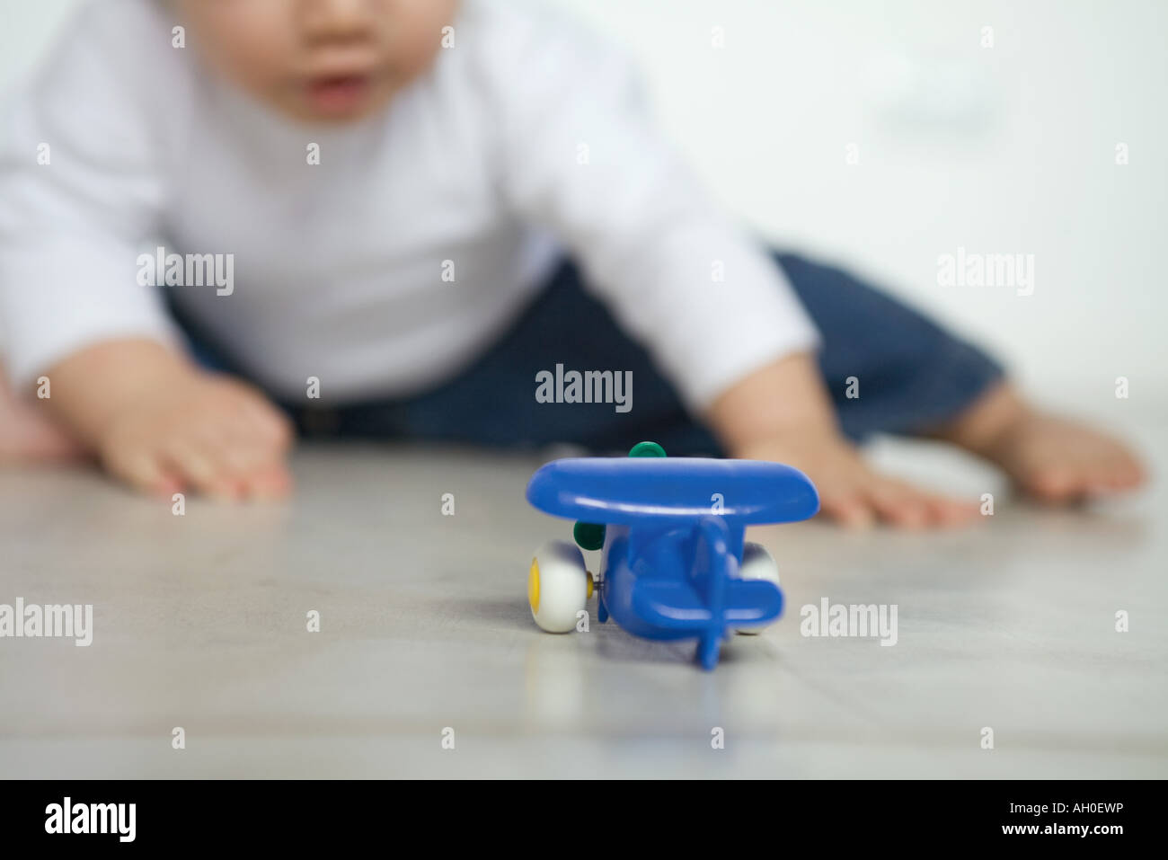 Toy airplane on floor, baby in background - Stock Image