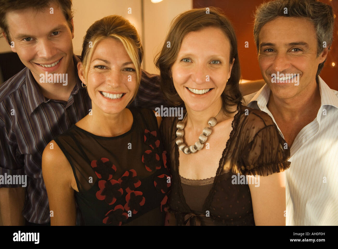 Four adult friends smiling at camera, group portrait - Stock Image