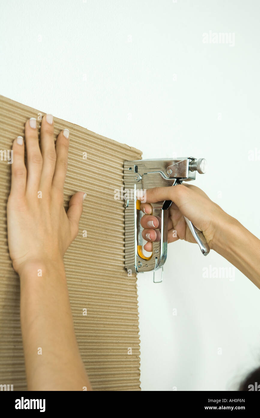 Woman stapling corrugated cardboard, cropped view of hands - Stock Image