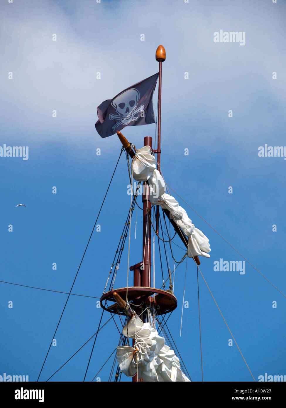 Skull and bones jolly roger pirates flag waving in the mast of a tall ship - Stock Image