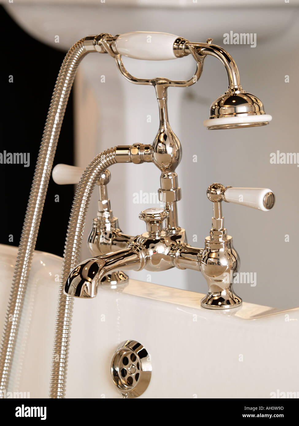 Classically designed crome steel mixing luxury bath faucet with showerhead on edge of bath - Stock Image