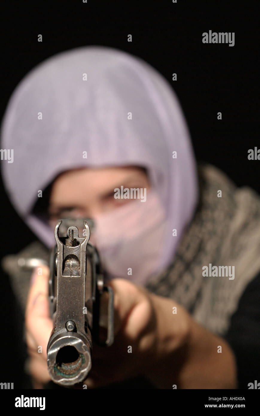 Female Extremist Fighter in Middle Eastern Dress with an AK47 Assault Rifle - Stock Image