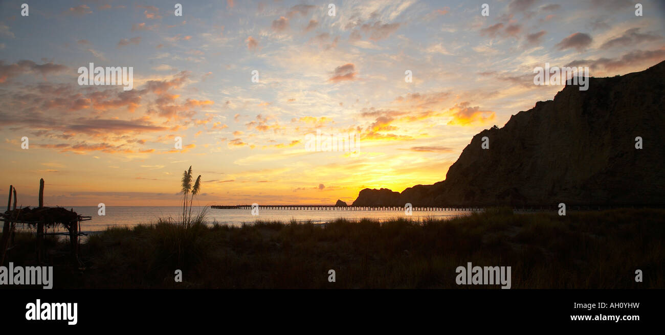 sunrise over sand dune and wharf at tolaga bay - Stock Image