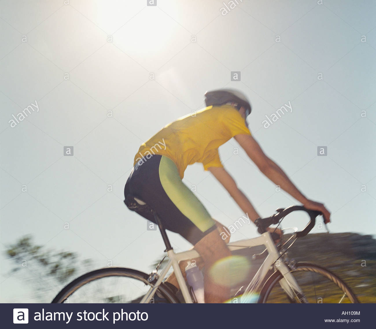 A man riding his bike on a sunny day - Stock Image