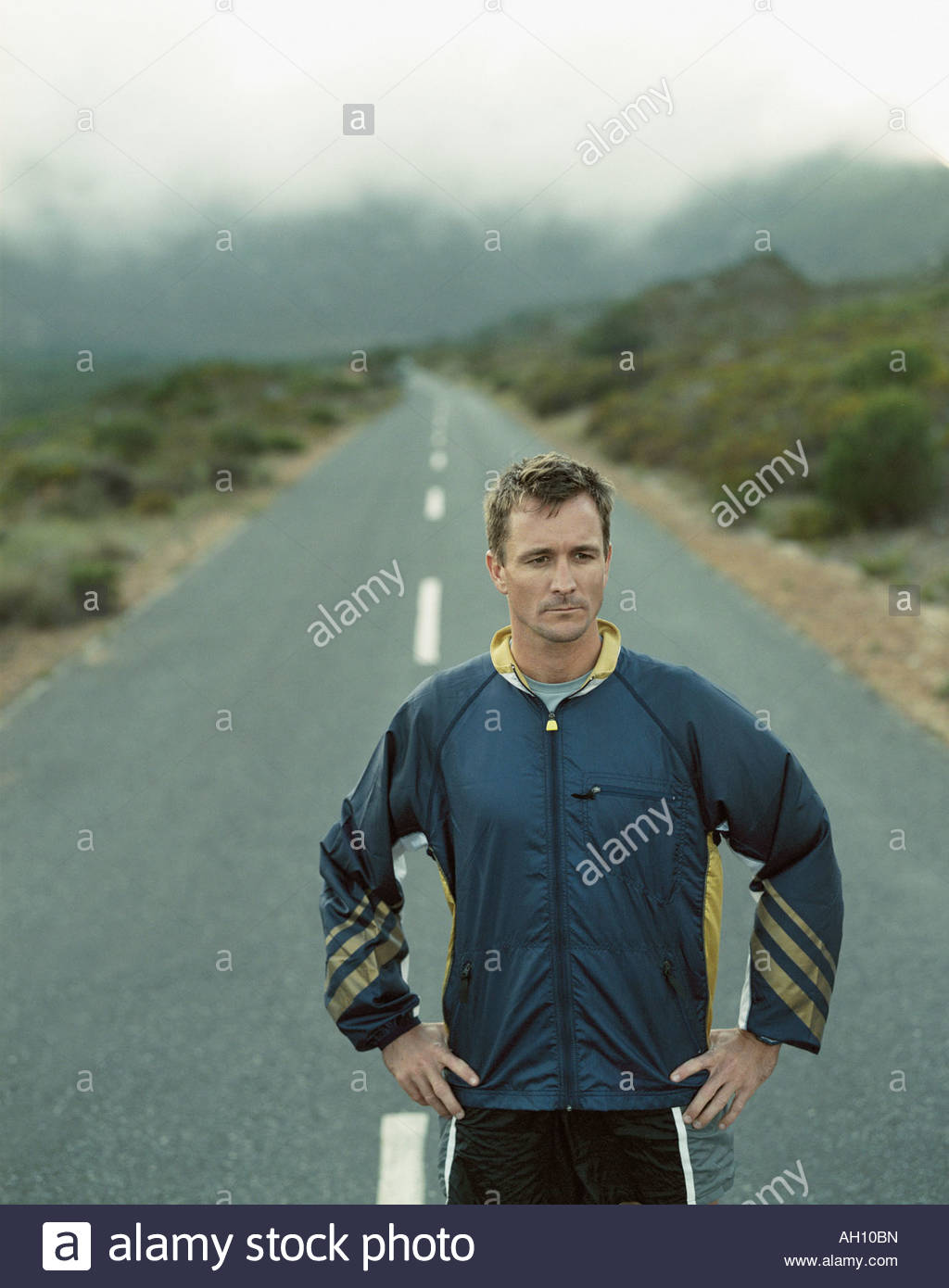 A stoic man standing on a desolate road - Stock Image