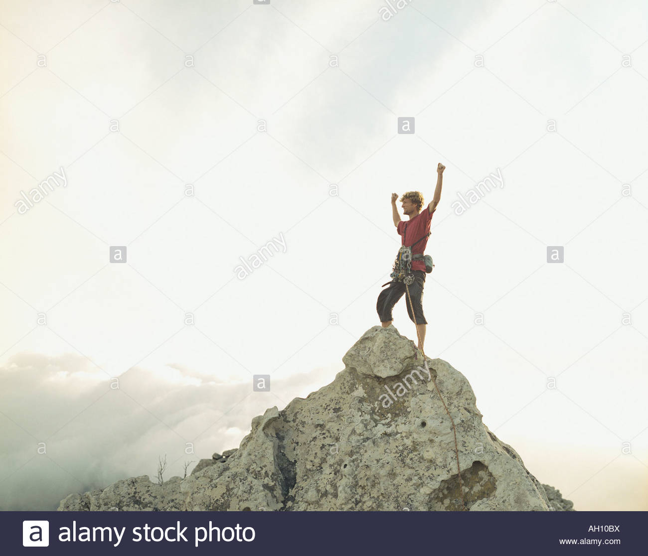 A climber at the top of a mountain victorious - Stock Image