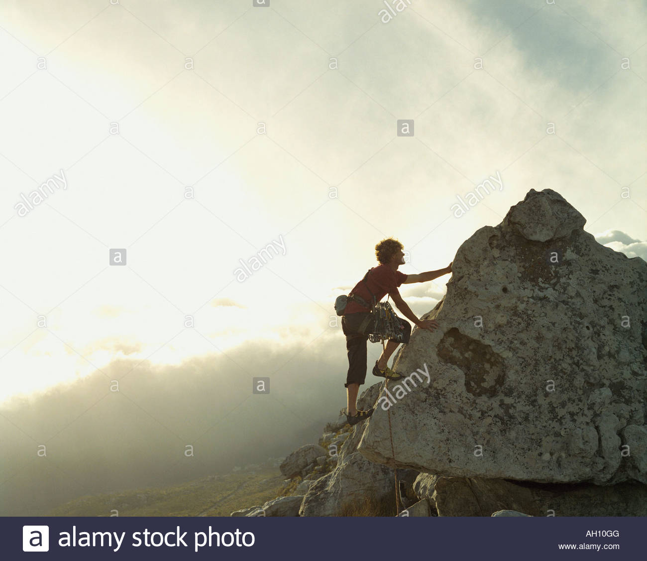 A mountain climber reaching the top of a mountain - Stock Image
