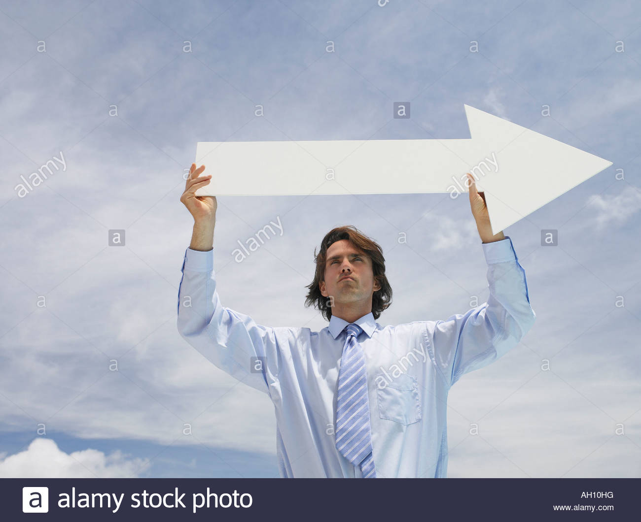Businessman outdoors holding blank arrow with sky in background - Stock Image
