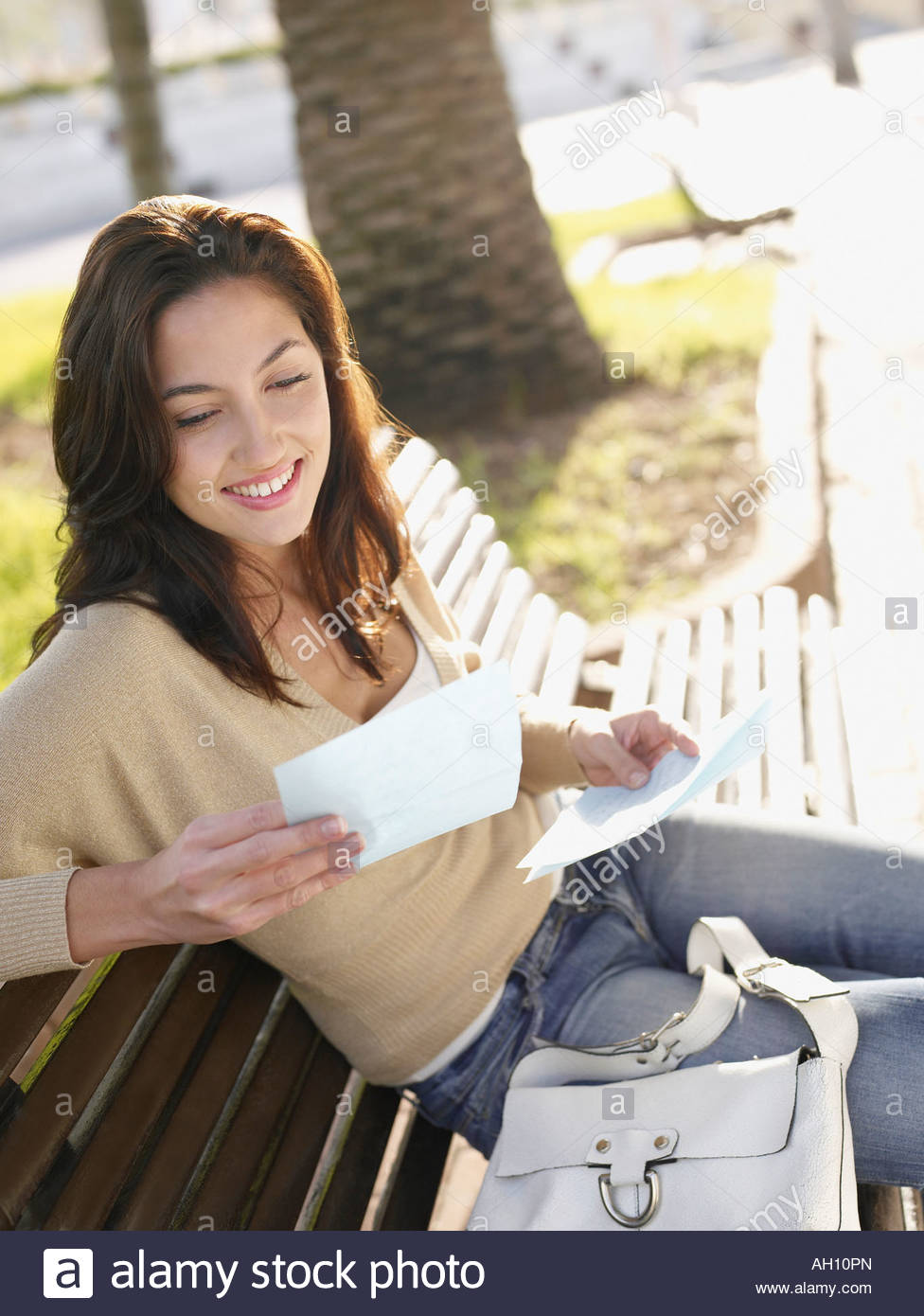 Woman sitting on wooden bench with personal letter smiling - Stock Image