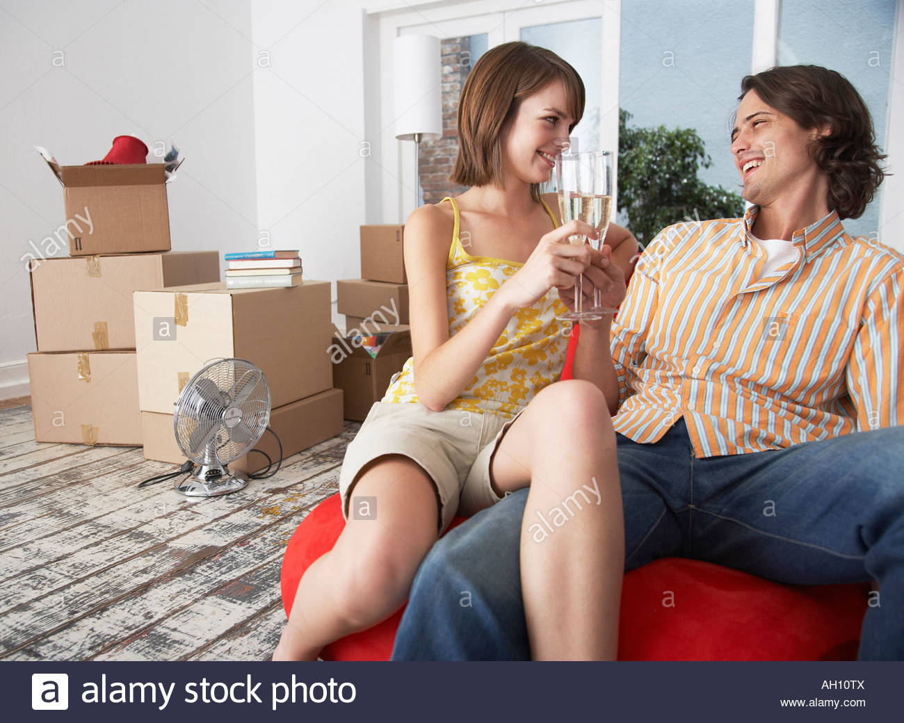 Couple with champagne in house with red chair celebrating - Stock Image