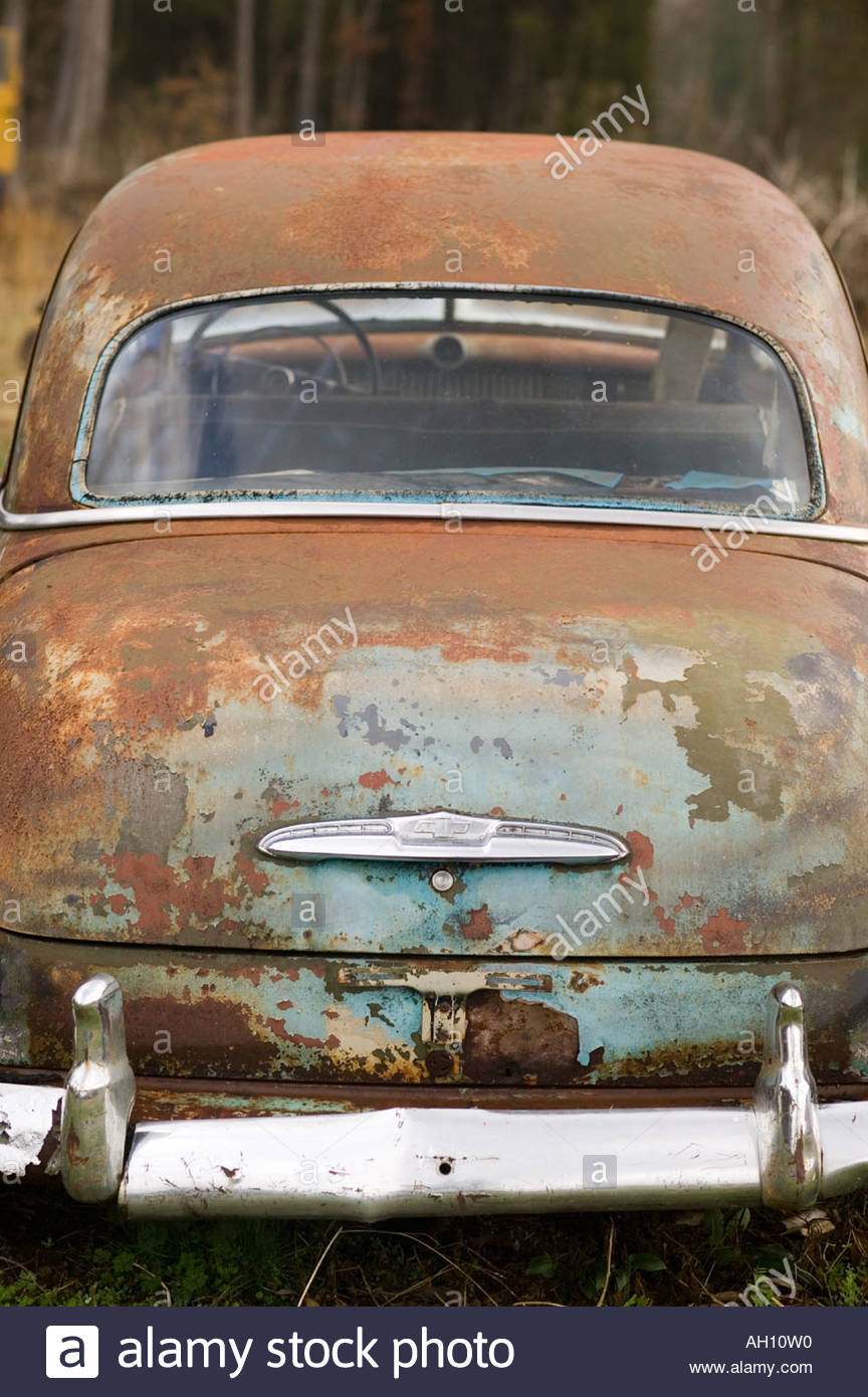 old rusted car with For Sale sign in the window sitting in a field ...