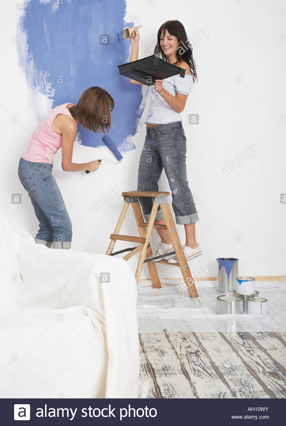 Two women painting room with thought balloon - Stock Image