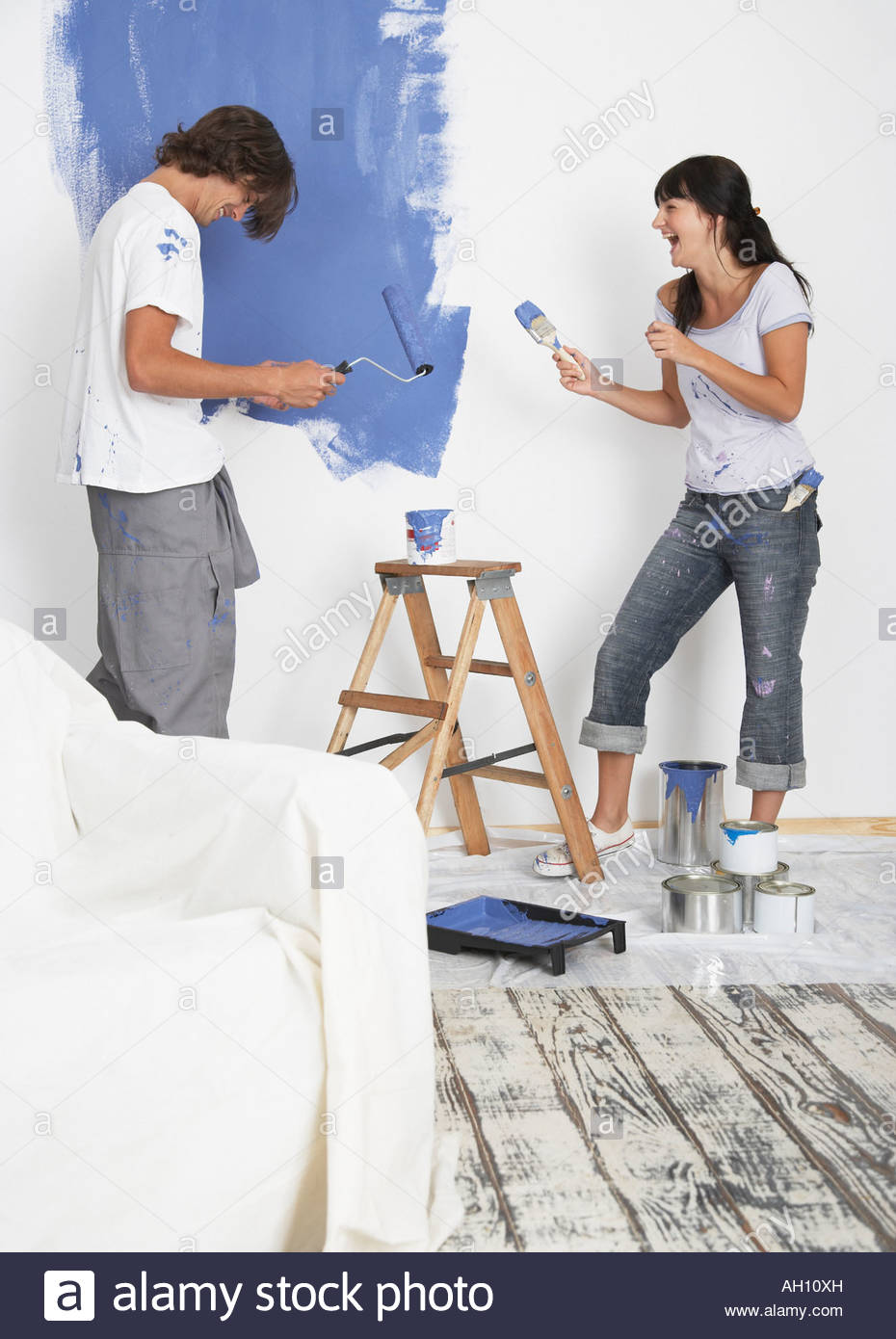 Man and woman playing with paint and laughing - Stock Image