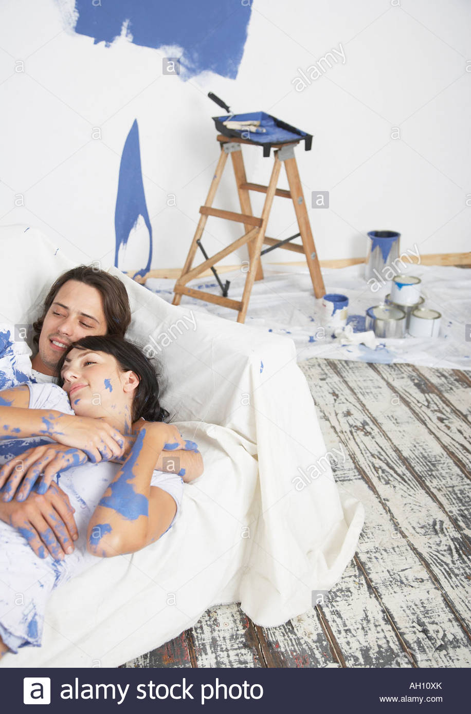 Man and woman on sofa with paint - Stock Image