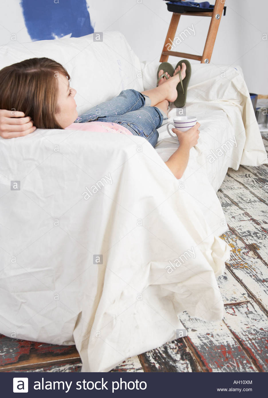 Woman on sofa with mug - Stock Image
