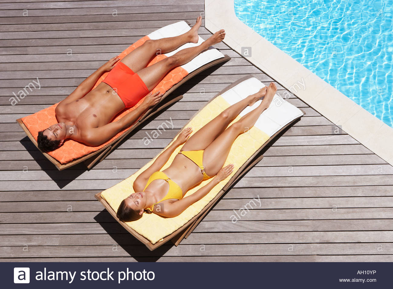 Man and woman sunbathing on pool deck - Stock Image