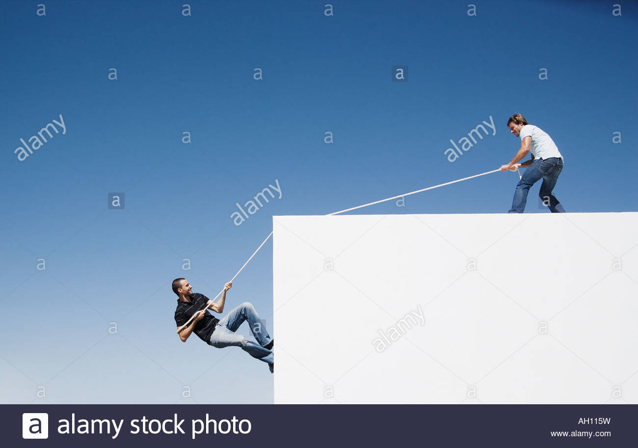 A man helping another man climb up a wall - Stock Image