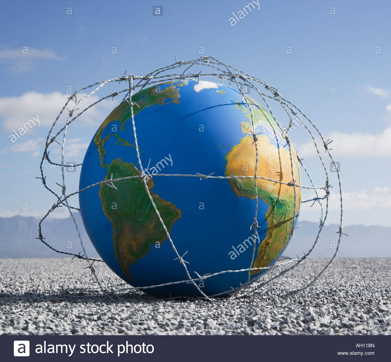 A globe entangled in barbed wire - Stock Image