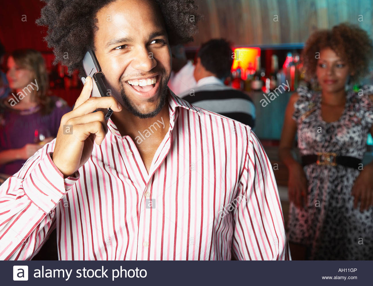 A man at a bar on his cellular phone - Stock Image
