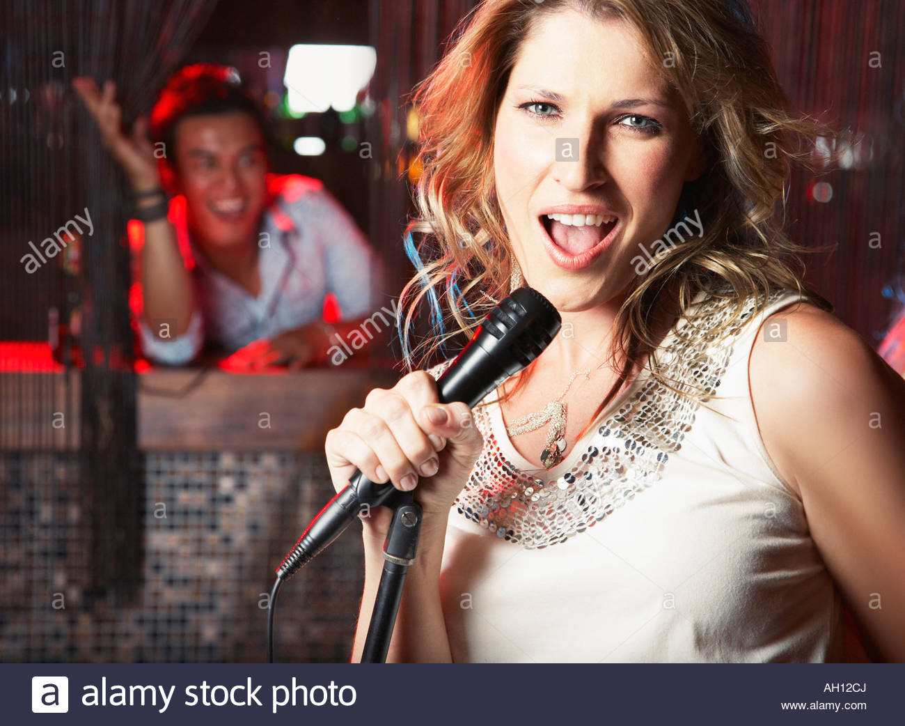 A woman singing at a club - Stock Image