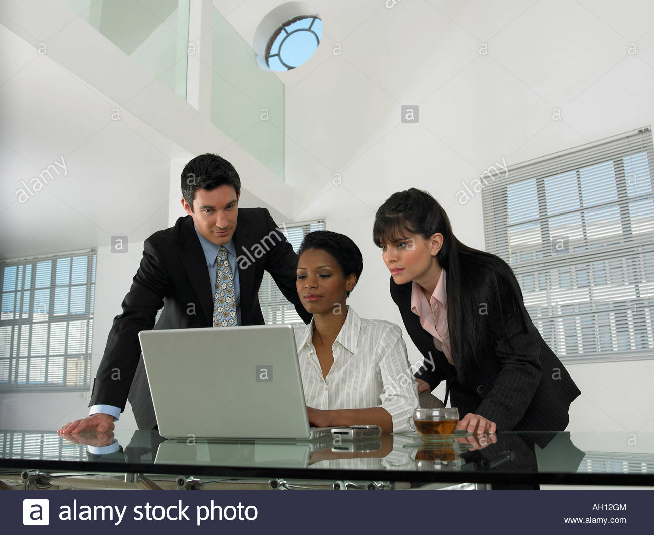 A businesswoman on a laptop with two co-workers behind her - Stock Image