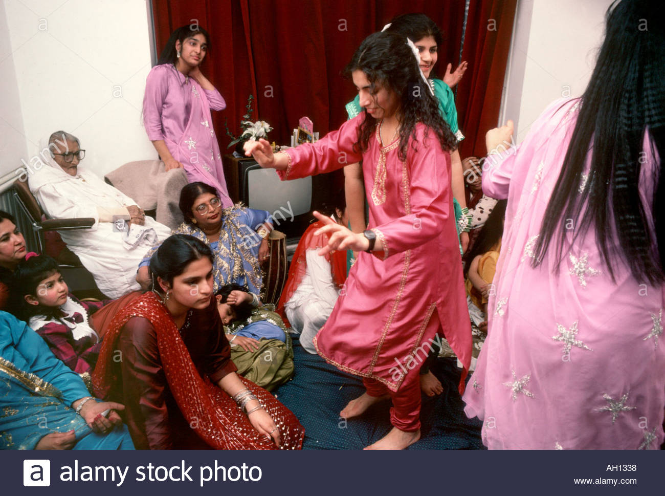 asian women dancing in living room at wedding reception at home uk