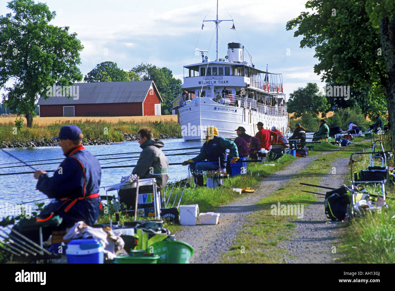 Passenger steamship passing line of pole fishermen while crossing Sweden on Gota Canal - Stock Image