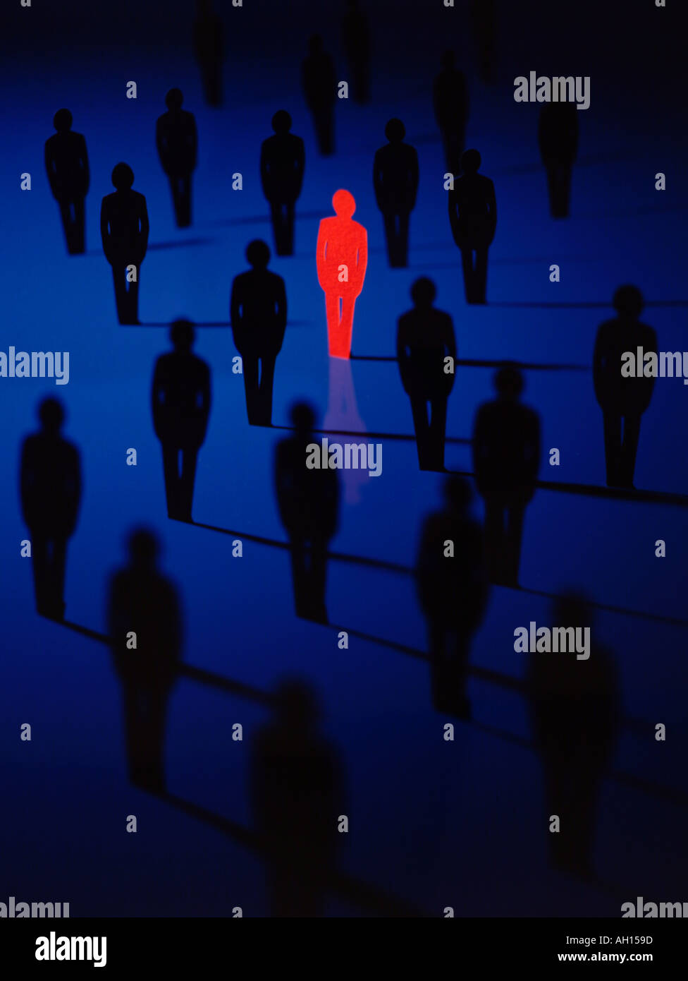 Solitary red person in a field of blue people - Stock Image