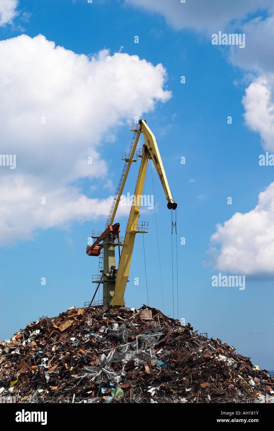 Harbour crane loading metal scrap in port - Stock Image