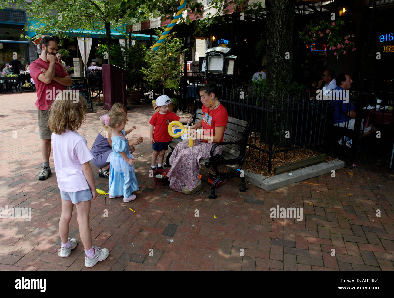 Street artist makes balloon animals for children on sidewalk, Asheville, North Carolina - Stock Image