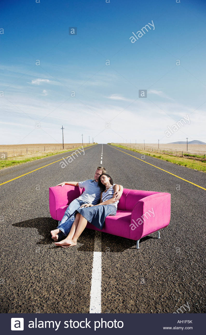 A couple relaxing on a couch in the road Stock Photo