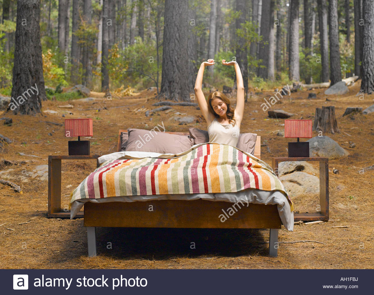 A woman stretching in a bed outdoors in the woods - Stock Image
