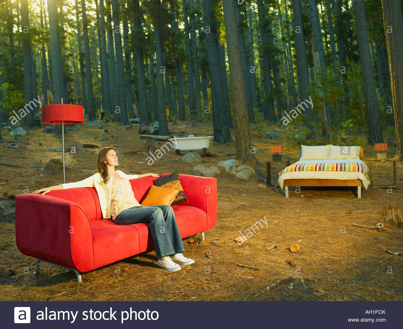 A woman with home furnishings sitting outdoors in the woods - Stock Image