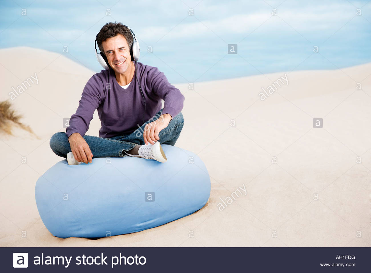 A man wearing headphones on a beanbag chair outdoors - Stock Image