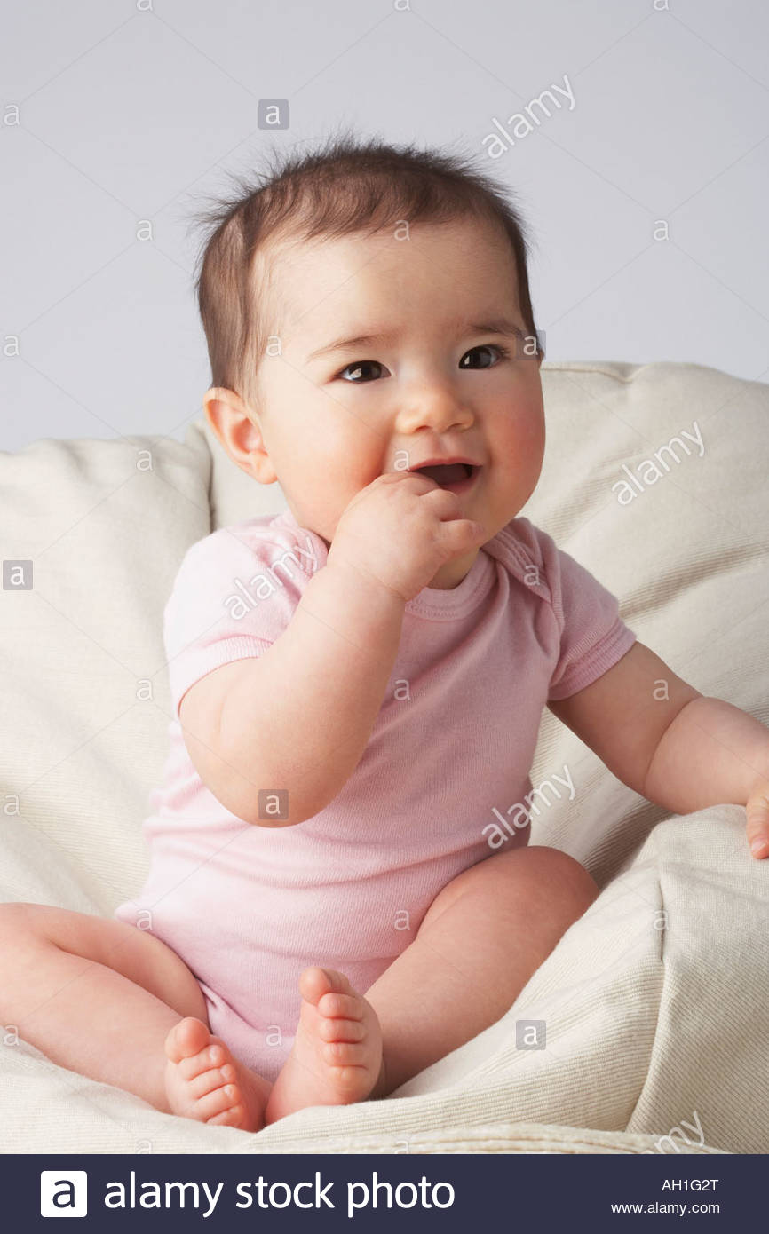 A baby in a beanbag chair - Stock Image
