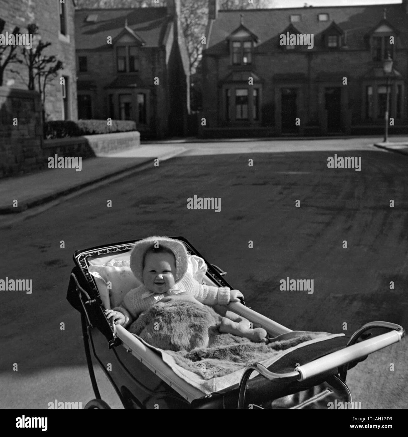 OLD VINTAGE FAMILY SNAPSHOT PHOTOGRAPH OF BABY GIRL IN PRAM IN MIDDLE OF EMPTY STREET - Stock Image